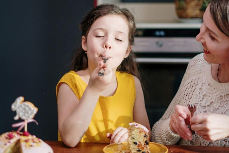 Child Eating Cake with Mother