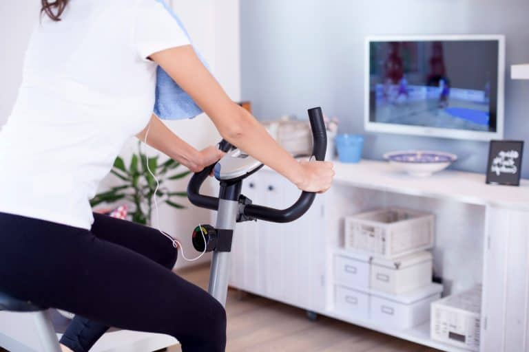Woman Cycling While Watching TV