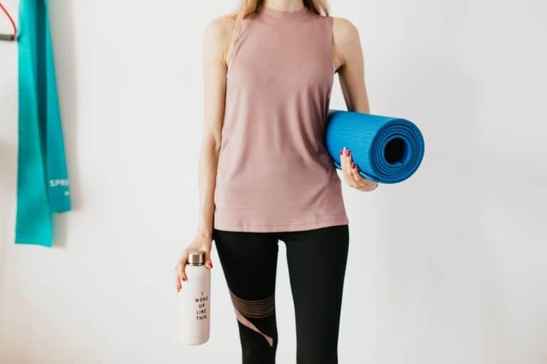 Woman Holding a Bottle and a Gym Mat